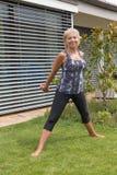 La femme supérieure de sourire s'exerce avec des haltères dans un montant Image libre de droits