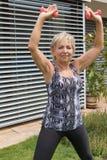 La femme supérieure de sourire s'exerce avec des haltères regardant Image stock