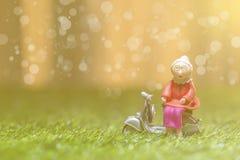 La femme supérieure de vieille poupée s'asseyent sur le fond de bokeh de moto Image stock