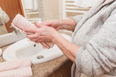 La femme supérieure essuie ses mains avec une serviette dans la salle de bains dans le temps de matin, plan rapproché images stock