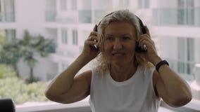 La femme supérieure est engagée dans le gymnase femme blonde écoutant la musique sur des écouteurs dans le gymnase banque de vidéos