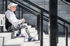 La femme supérieure gaie détendant après s'être élevé sur le stade fait un pas extérieur Images stock