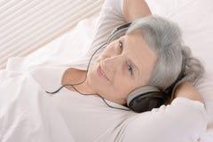 La femme supérieure heureuse écoutent une musique dans des écouteurs se reposant dans un lit photographie stock libre de droits