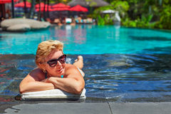 La femme supérieure heureuse retirée détendent dans la piscine Photo stock
