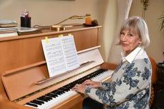 La femme supérieure joue le piano photo libre de droits