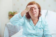 La femme supérieure a obtenu un mal de tête photos stock