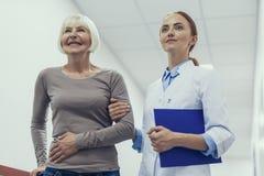 La femme supérieure ravie apprécie l'aide de docteur images stock