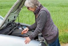 La femme supérieure s'occupe du niveau d'huile dans la voiture Photos libres de droits
