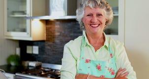 La femme supérieure se tenant avec des bras a croisé dans la cuisine 4k banque de vidéos