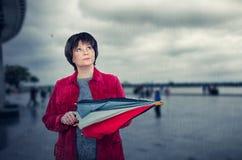La femme supérieure se tient sous la pluie soudaine en Europe Photographie stock libre de droits