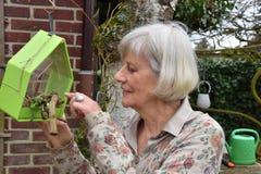La femme supérieure vérifie la volière dans son jardin photo libre de droits