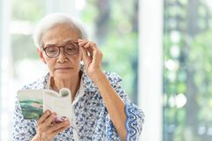 La femme sup?rieure asiatique lisant un livre d?tendu ? la maison, femme ag?e d?pensent leur livre de lecture de temps libre photo stock