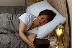 La femme supérieure ne peut pas dormir à la nuit tout en regardant l'horloge Photo libre de droits