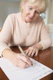 La femme supérieure signant pour la dernière fois et testament à la maison Photographie stock libre de droits