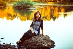 La femme sur la pierre par la rivière Photos libres de droits