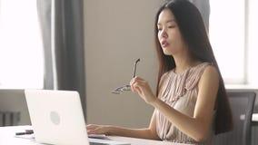 La femme surchargée d'affaires d'Asiatique Stressed tenant des verres sentent la fatigue oculaire banque de vidéos