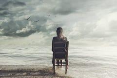La femme surréaliste regarde la séance infinie sur une chaise à l'intérieur de la mer Photographie stock libre de droits