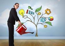 La femme tenant la boîte d'arrosage et dessin des graphiques de gestion sur l'usine s'embranche sur le mur Images stock