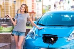 La femme tenant des clés s'approchent de sa voiture hybride images stock