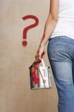 La femme tenant la peinture peut avec la question peinte Mark On Wall Photographie stock libre de droits