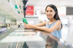 La femme tenant le téléphone portable en test dedans contre à l'aéroport Image libre de droits