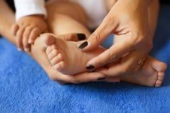 La femme a tendrement embrassé les jambes du ` s de bébé Photographie stock libre de droits