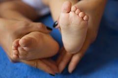 La femme a tendrement embrassé les jambes du ` s de bébé Photos libres de droits