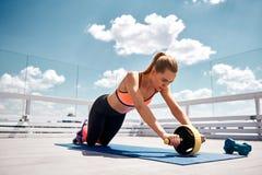 La femme tendue s'exerce avec le rouleau d'ABS sur le balcon photos stock