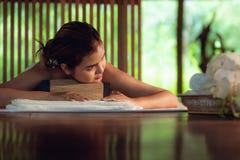La femme thaïlandaise est corps de thérapies avec le massage de station thermale et la relaxation menteuse dans le massage d'affa image libre de droits