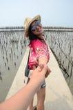 La femme thaïlandaise mènent quelqu'un par la main et se tiennent sur le pont en passage couvert Photos libres de droits