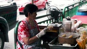 La femme thaïlandaise nettoie et coupe le fruit sur le marché de nourriture Mouvement lent banque de vidéos