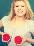 La femme tient des agrumes de pamplemousse sur le sein Photos stock