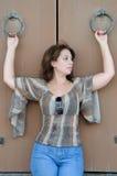 La femme tient des anneaux de fer sur les portes en bois Image stock