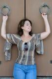 La femme tient des anneaux de fer sur les portes en bois Images stock