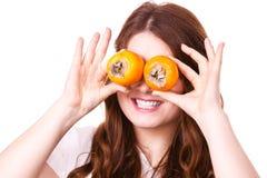 La femme tient des fruits de kaki de kaki sur des yeux, d'isolement Image libre de droits