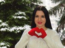 La femme tient des mains sous forme de coeur Image libre de droits