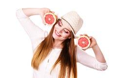 La femme tient deux halfs d'agrumes de pamplemousse dans des mains Image stock