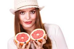 La femme tient deux halfs d'agrumes de pamplemousse dans des mains Photographie stock libre de droits