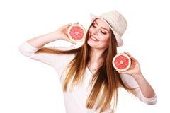 La femme tient deux halfs d'agrumes de pamplemousse dans des mains Photos libres de droits