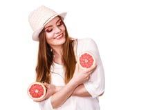 La femme tient deux halfs d'agrumes de pamplemousse dans des mains Images stock