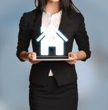 La femme tient le comprimé avec l'icône à la maison Image libre de droits