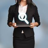 La femme tient le comprimé avec l'icône de loupe Photographie stock