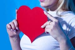La femme tient le grand symbole rouge d'amour de coeur Photo stock