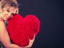 La femme tient le grand symbole rouge d'amour de coeur Photos libres de droits