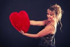 La femme tient le grand symbole rouge d'amour de coeur Image stock