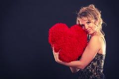 La femme tient le grand symbole rouge d'amour de coeur Images stock