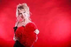 La femme tient le grand symbole rouge d'amour de coeur Photographie stock