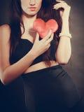 La femme tient le symbole rouge d'amour de coeur Photos stock