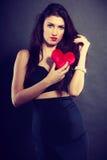 La femme tient le symbole rouge d'amour de coeur Image stock