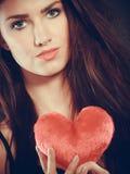 La femme tient le symbole rouge d'amour de coeur Photographie stock